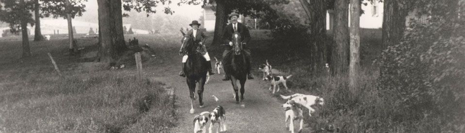 Chevy Chase Maryland Man and Woman on horseback with dogs riding to Fox Hunt